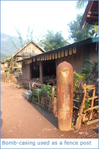 An old bomb casing being used as a fence post in Muang Ngoi