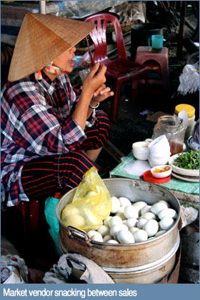 Photo of market vendor snacking between sales in Hoi An, Vietnam
