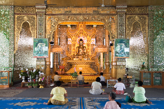 A golden Buddha watches people meditate and take naps.