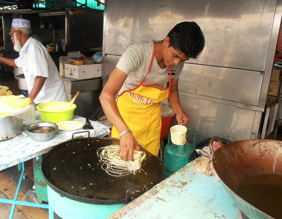A stallholder making one of the bazaar's more unusual offerings, 'roti jala'.