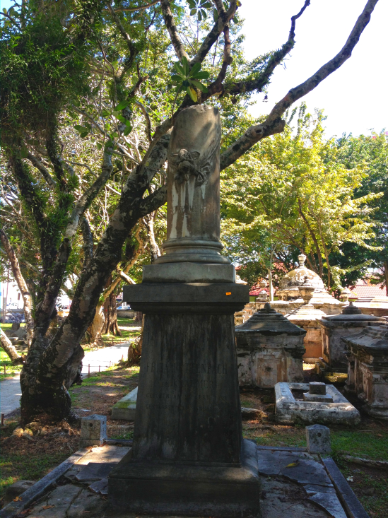 A headless angel atop a plinth dominates the dead, worthy of a gothic horror novel.