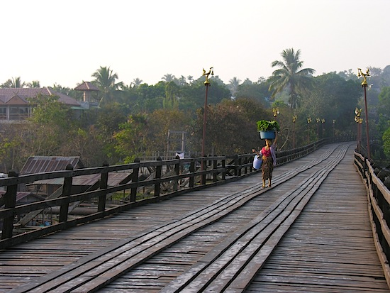 A Mon woman walks across the wooden bridge with her produce.