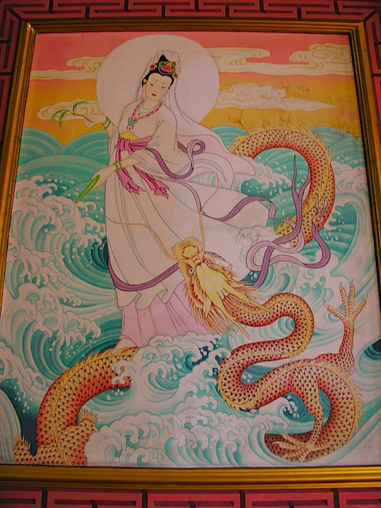 A mural shows Kuan Im with vase, willow branch ... and dragon.