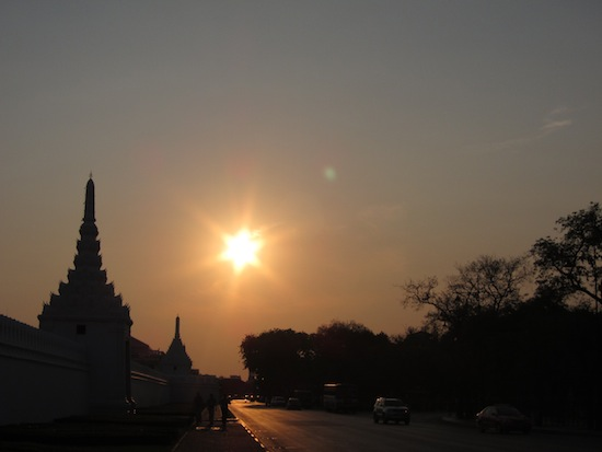 A big sun sets over the gates of the Grand Palace.