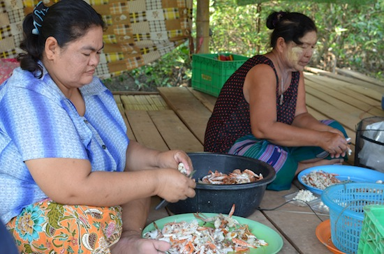 Village women prepare boxes of crab meat to sell.