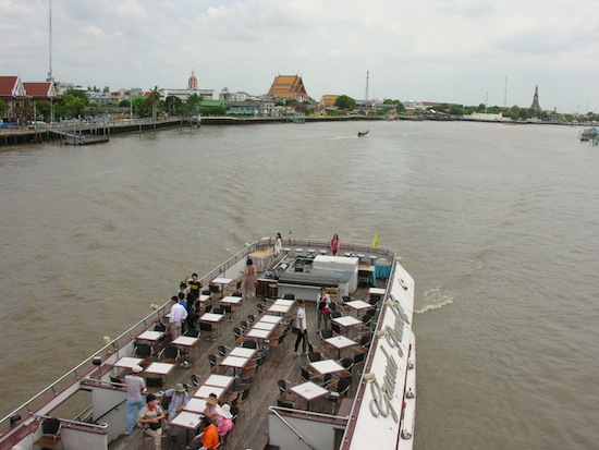 A tourist cruise boat glides under Memorial Bridge, with Santa Cruz Church (left), Wat Kalayanamit and Wat Arun all visible.